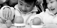 昨日春分,杭州小荧星艺术幼儿园内,小朋友在体验立蛋游戏。 拍友 徐军勇 摄 - 浙江新闻网