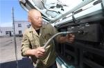图为金海渊正在使用回气装置为车辆导气。 董美巧 摄 - 浙江新闻网