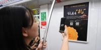图为:一位乘客被让座有礼贴牌吸引。 王刚 摄 - 浙江网