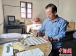 章明夫在整理古钱币 施紫楠 摄 - 浙江新闻网