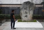 图为:一位参观者在细菌战死难民众纪念碑前驻足参观。 王刚 摄 - 浙江新闻网
