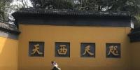 图为杭州灵隐飞来峰景区大门口,一位游客在自拍。 严格 摄 - 浙江新闻网