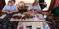 村民们在文化礼堂内制作板龙刻纸 范宇斌 摄 - 浙江网